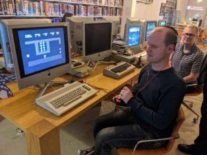 Ich sitze vor einem alten C64, meine linke Hand hält den Steuerknüppel eines Joysticks und um mich herum stehen drei/vier Leute und schauen zu | Bild Copyright Christian Ohrens, Location Retro Spiele Club Hamburg
