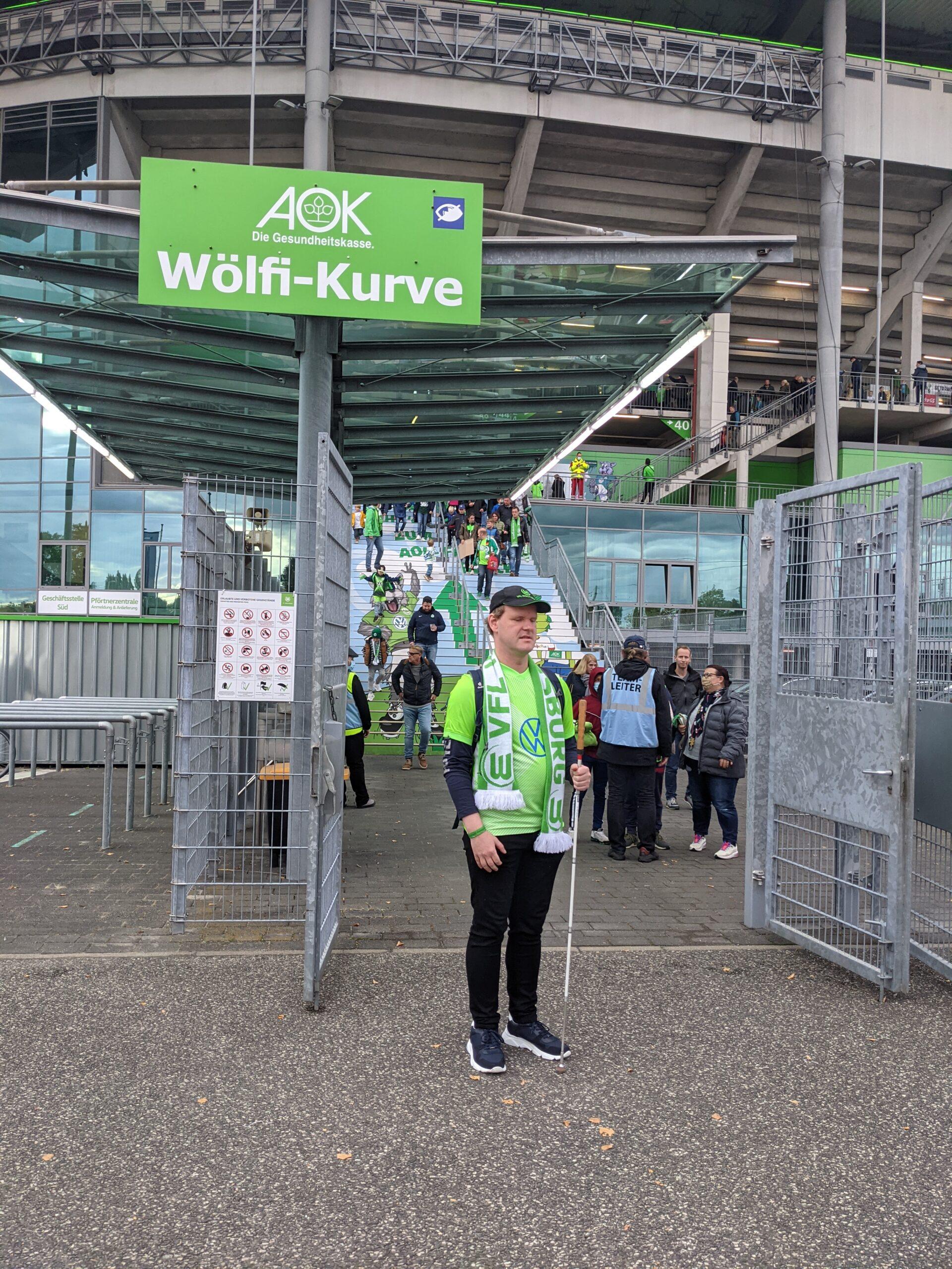 Ich stehe, bekleidet mit einem VFL-Trikot, einem Schal sowie einer Cap, vor dem Eingang der Volkswagen-Arena